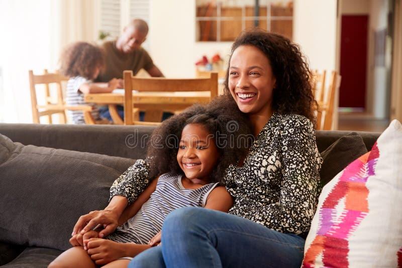 Mère et fille s'asseyant sur Sofa At Home Watching Movie à la TV ensemble photos libres de droits