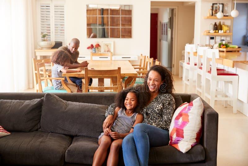 Mère et fille s'asseyant sur Sofa At Home Watching Movie à la TV ensemble photographie stock libre de droits