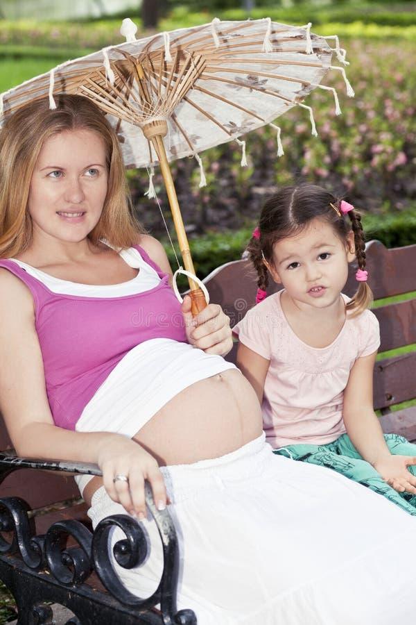 Mère et fille s'asseyant sur un banc de parc image libre de droits