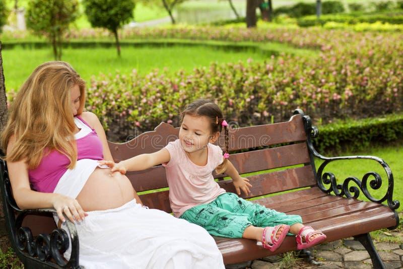 Mère et fille s'asseyant sur un banc de parc photographie stock libre de droits
