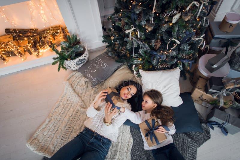 Mère et fille se trouvant avec des cadeaux sous l'arbre de Noël, vue supérieure images libres de droits