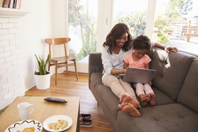 Mère et fille Sit On Sofa At Home à l'aide de l'ordinateur portable photographie stock libre de droits