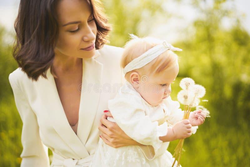 Mère et fille soufflant au pissenlit photographie stock