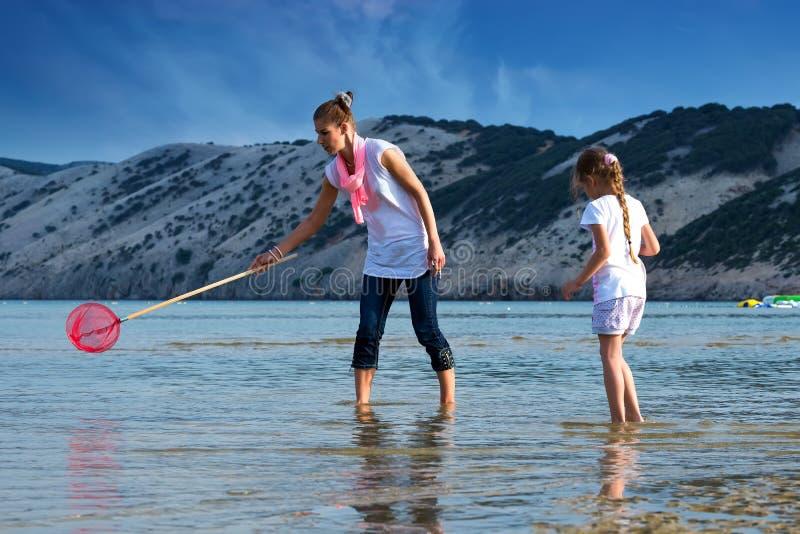 Mère et fille sur la pêche de plage photos stock