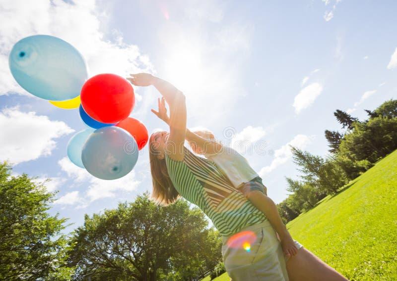 Mère et fille tenant des ballons en parc photo libre de droits