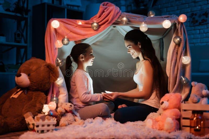 Mère et fille tenant la lampe-torche que leurs mains dans l'oreiller logent tard la nuit à la maison images libres de droits