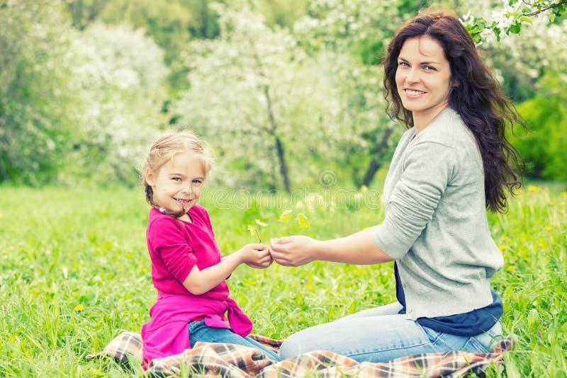 Mère et fille tenant peu de plante verte dans des mains photographie stock libre de droits