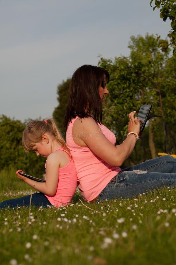 Mère et fille travaillant à un comprimé photo stock