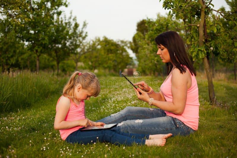 Mère et fille travaillant à un comprimé photos stock