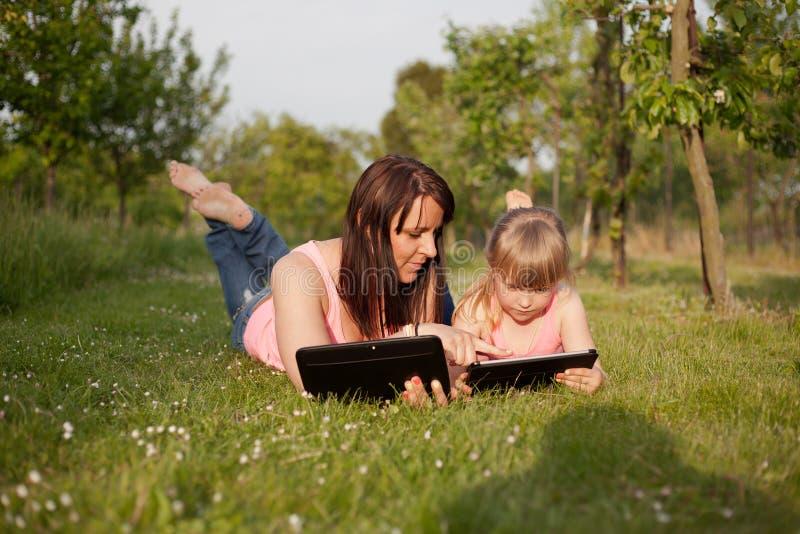 Mère et fille travaillant à un comprimé photographie stock