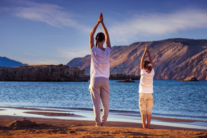 Mère et fille, yoga sur la plage tôt le matin photos libres de droits