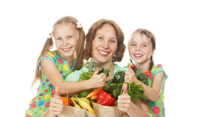 Mère et filles heureuses de famille avec des sacs des légumes photo stock