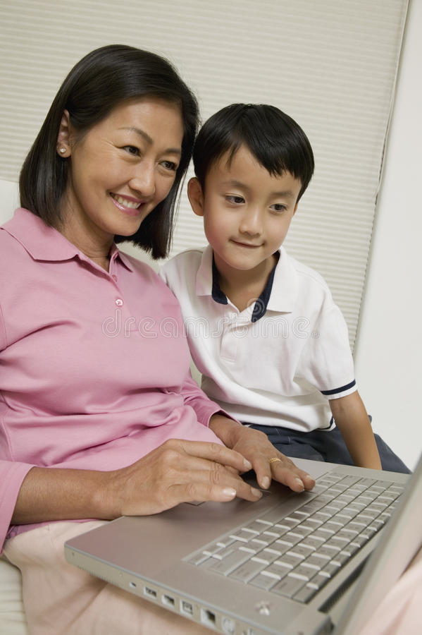 Mère et fils à l'aide de l'ordinateur portable dans le salon image libre de droits
