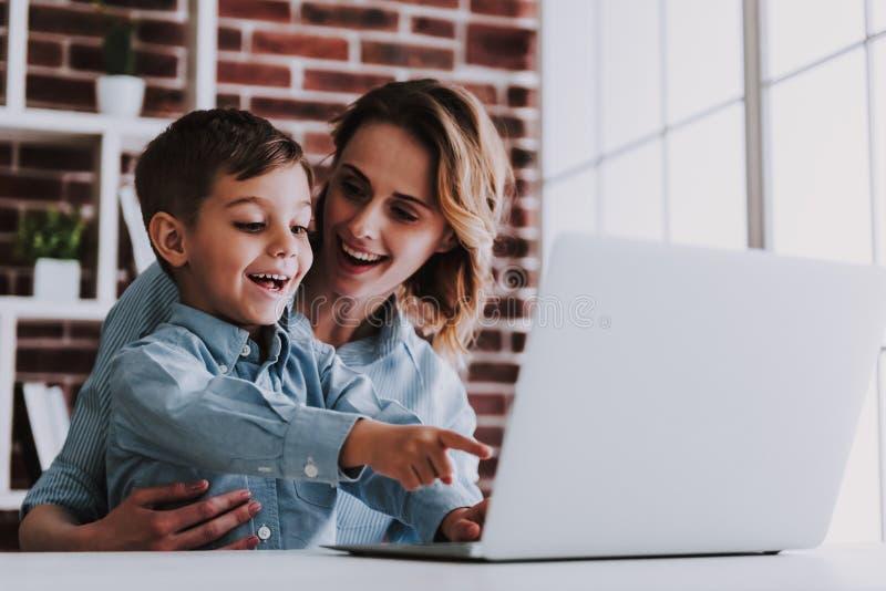 Mère et fils à l'aide de l'ordinateur portable ensemble à la maison photo stock