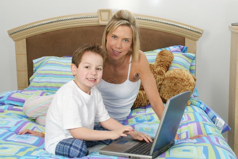 Mère et fils avec l'ordinateur portatif dans le bâti photographie stock