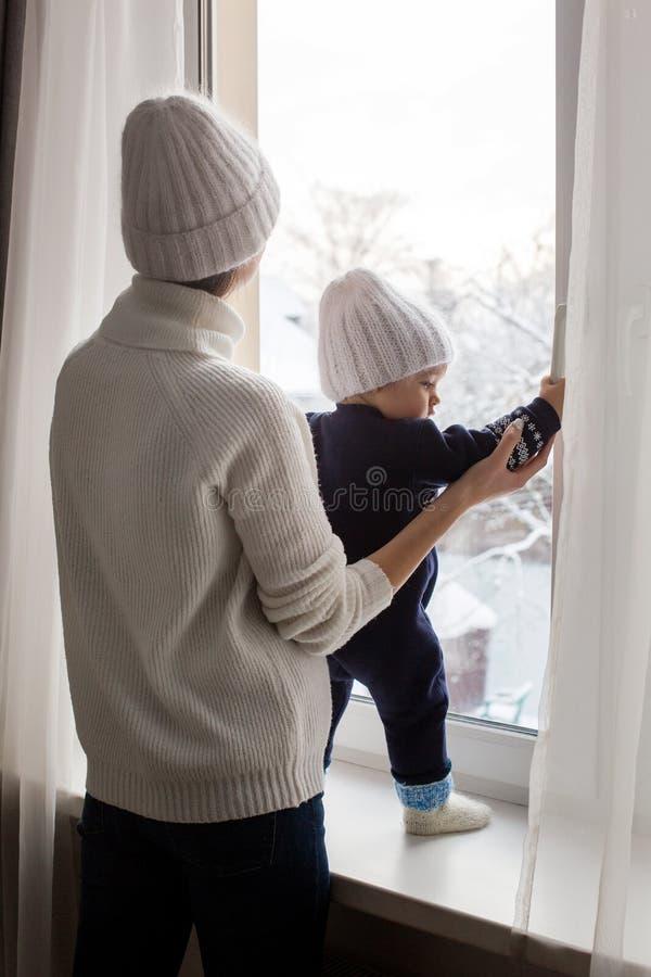 Mère et fils dans des chapeaux se tenant à la fenêtre image stock