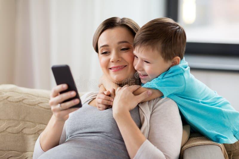 Mère et fils enceintes avec le smartphone à la maison images libres de droits