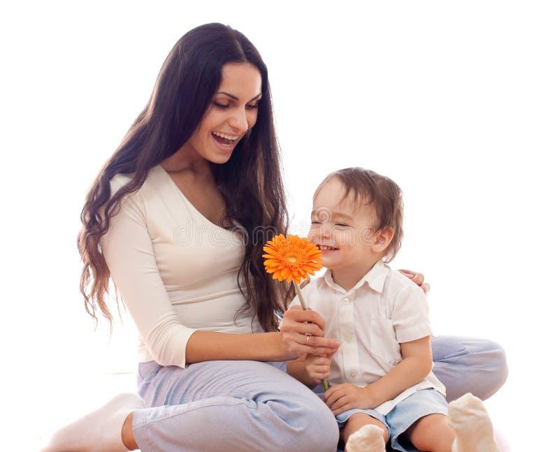 Mère et fils heureux avec la fleur ensemble d'isolement photo stock