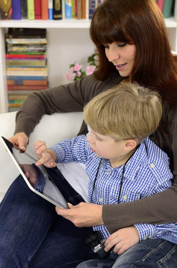 Mère et fils jouant avec la tablette digitale images stock