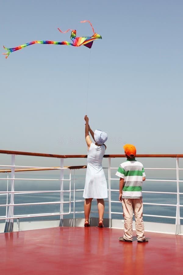 Mère et fils jouant avec le cerf-volant multicolore image stock
