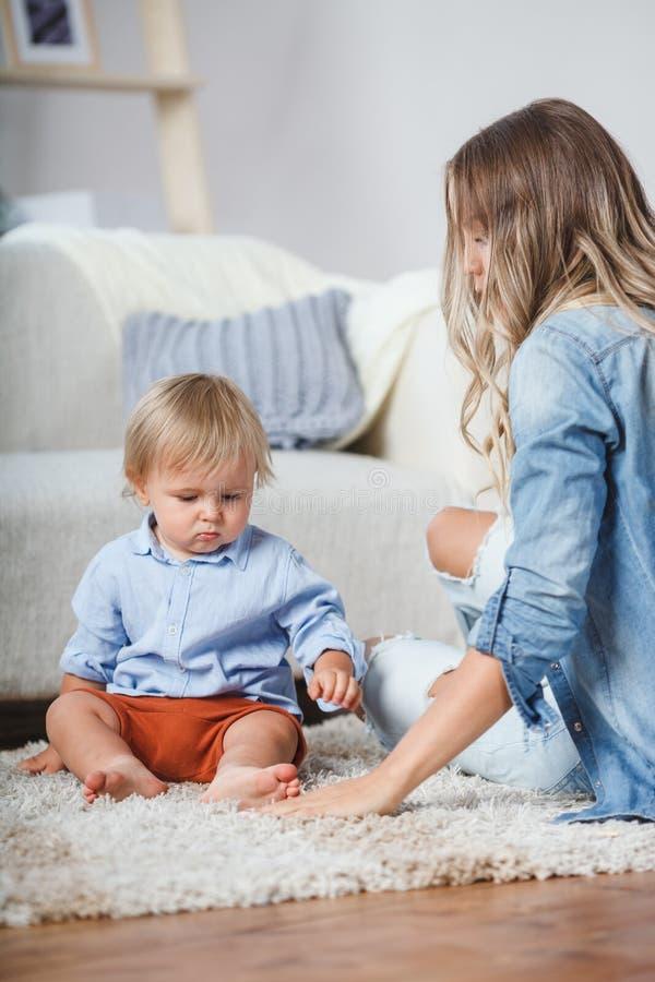 Mère et fils jouant sur le tapis près du sofa images libres de droits