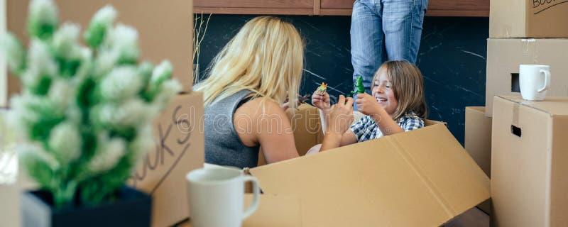 Mère et fils jouant tandis que le père regarde le mobile image stock