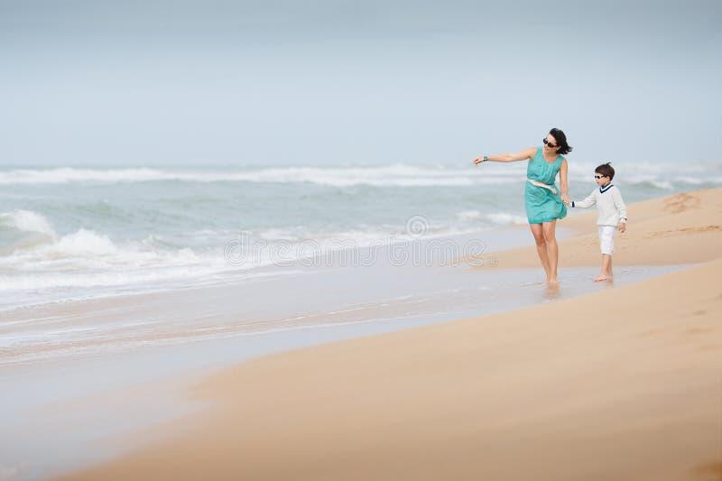 Mère et fils marchant le long d'une plage tropicale image stock