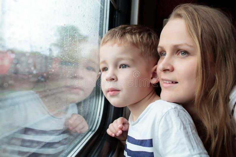 Mère et fils regardant par une fenêtre de train images stock