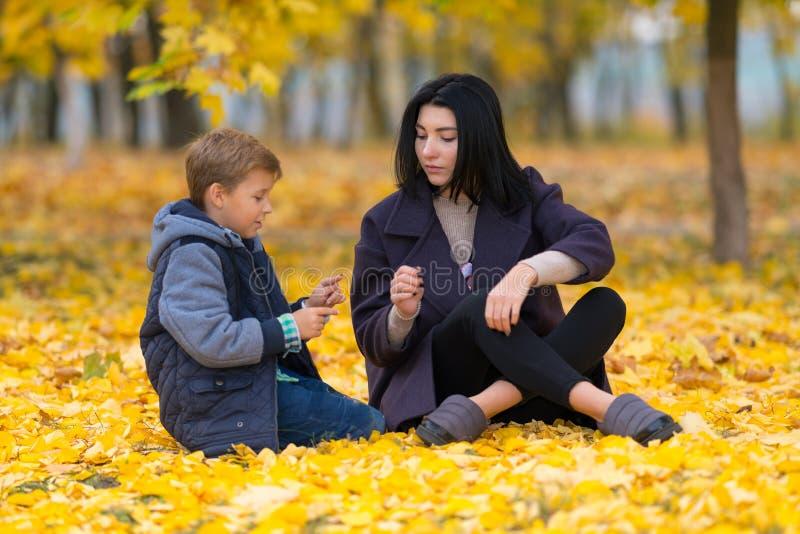 Mère et fils s'asseyant parmi les feuilles jaunes de chute photos libres de droits