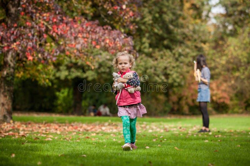 Mère et igirl ayant l'amusement dans le parc, filles bouclées mignonnes blondes marchant à partir de la mère avec ses jouets, fam image libre de droits