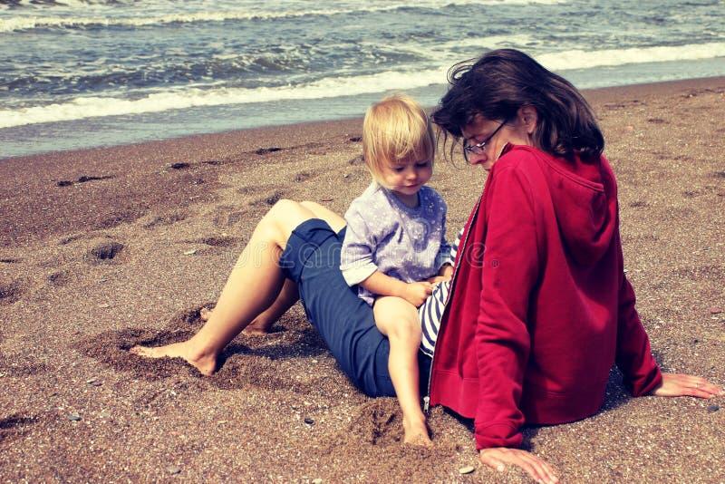 Mère et jeune fille s'asseyant sur la plage photos stock