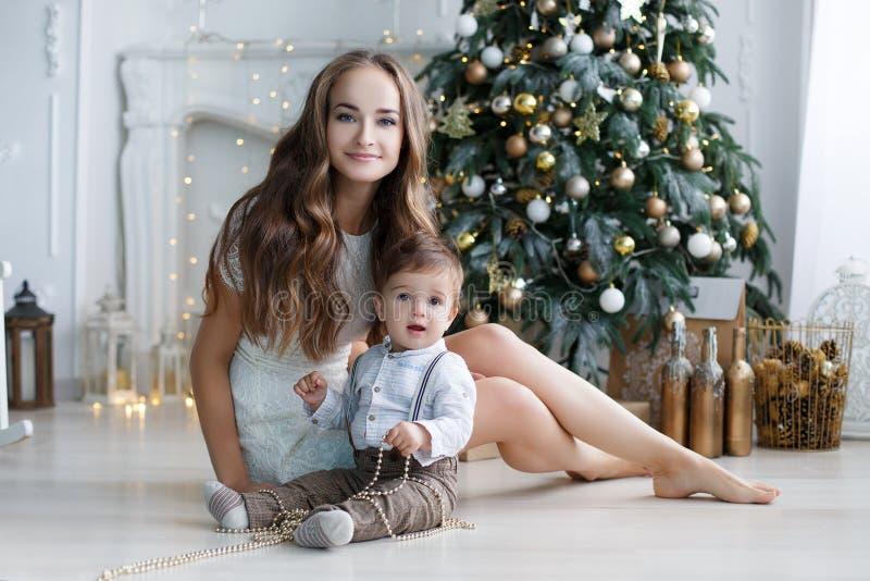 Mère et jeune fils à la maison près d'arbre de Noël photographie stock libre de droits