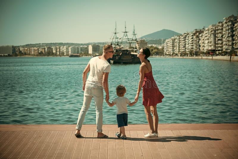 Mère et père allant embrasser près de leur enfant La famille heureuse passent le temps ensemble, fond de mer Parents avec le fils image libre de droits