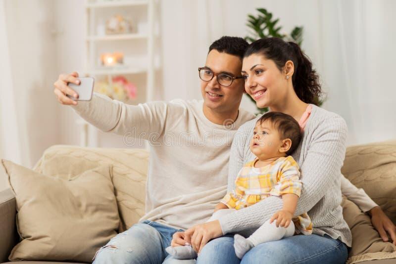 Mère et père avec le bébé prenant le selfie à la maison images libres de droits