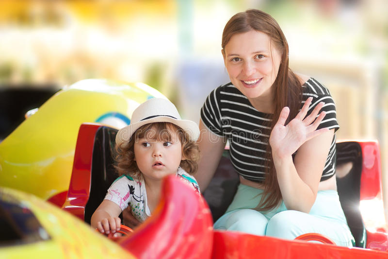 Mère et petit enfant dans le parc à thème, carrousel électrique de monte de rond point photographie stock libre de droits