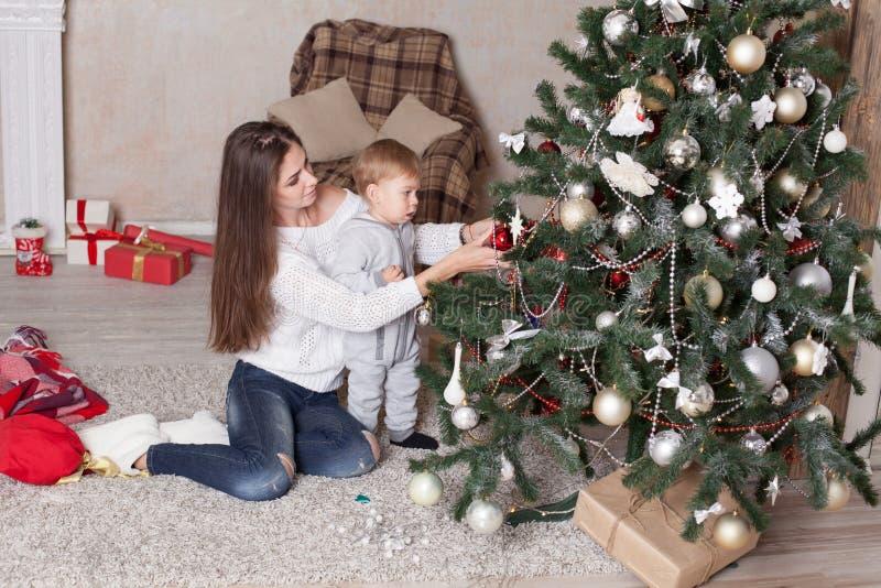 Mère et petit garçon à l'arbre de Noël avec les cadeaux 1 photos stock