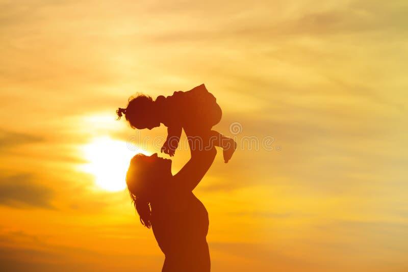 Mère et petit jeu de fille au coucher du soleil photo stock