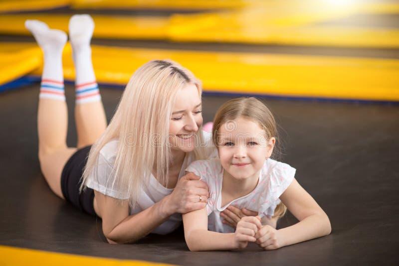 Mère et petite fille jouant au terrain de jeu et se trouvant sur un trempoline photo libre de droits