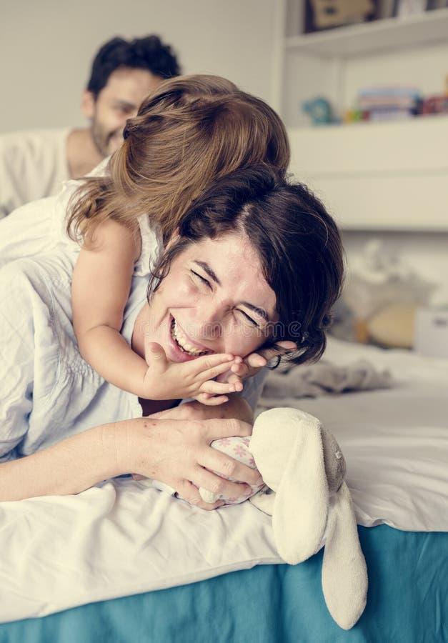 Mère et petite fille jouant sur le lit photos stock