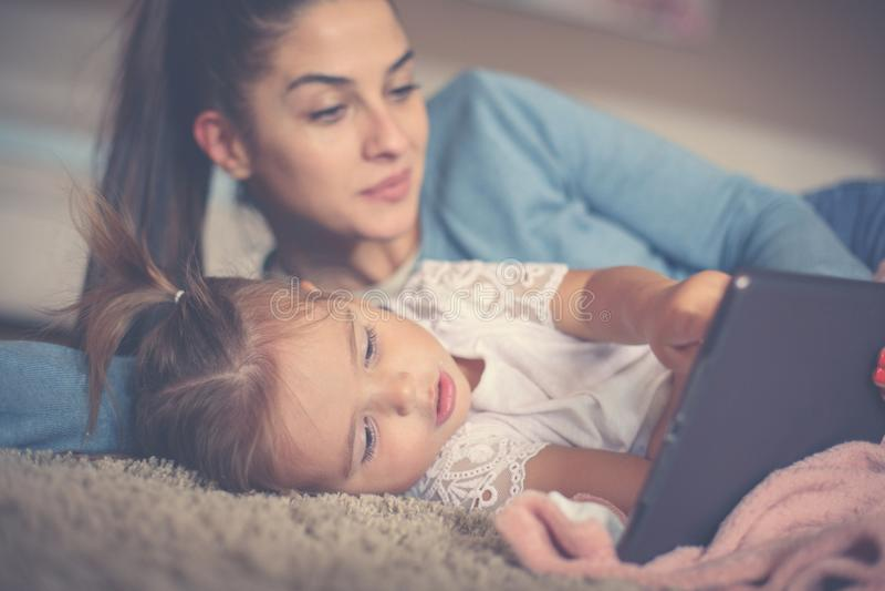 Mère et petite fille mettant en oeuvre à la maison et employant iPod Cl image stock
