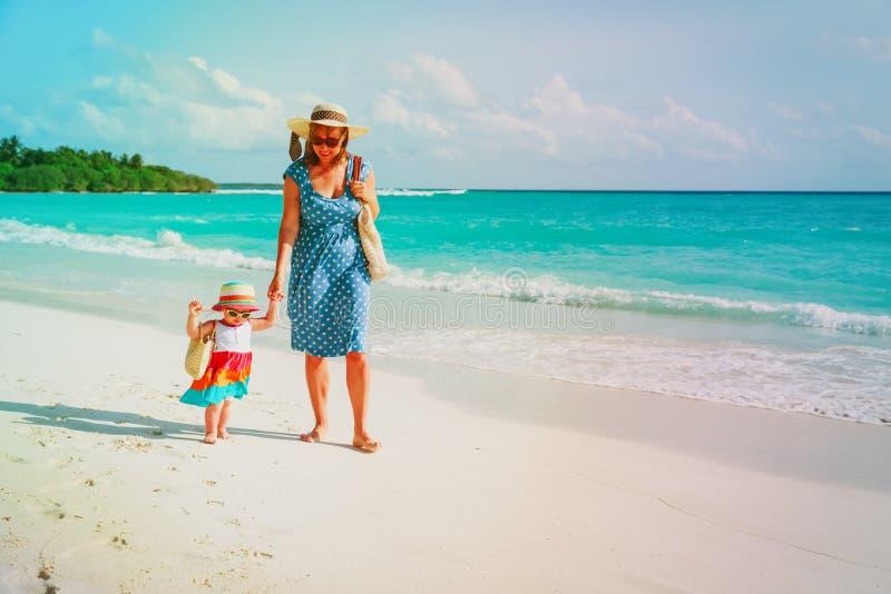 Mère et petite fille mignonne marchant sur la plage photo libre de droits