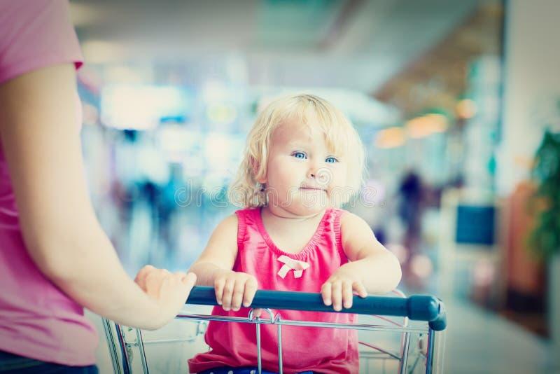 Mère et petite fille mignonne sur le chariot de bagage dedans images stock