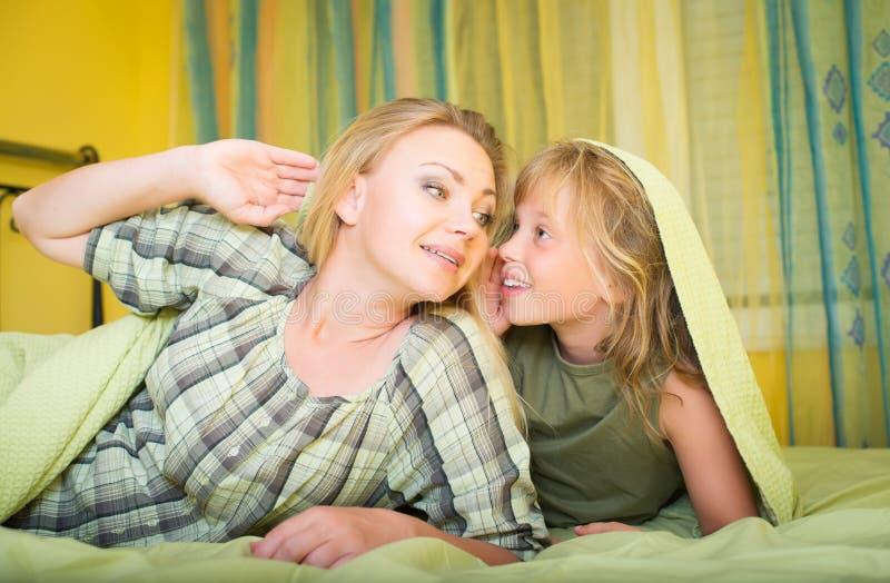 Mère et petite fille se situant le lit et en parlant famille bedtime photographie stock
