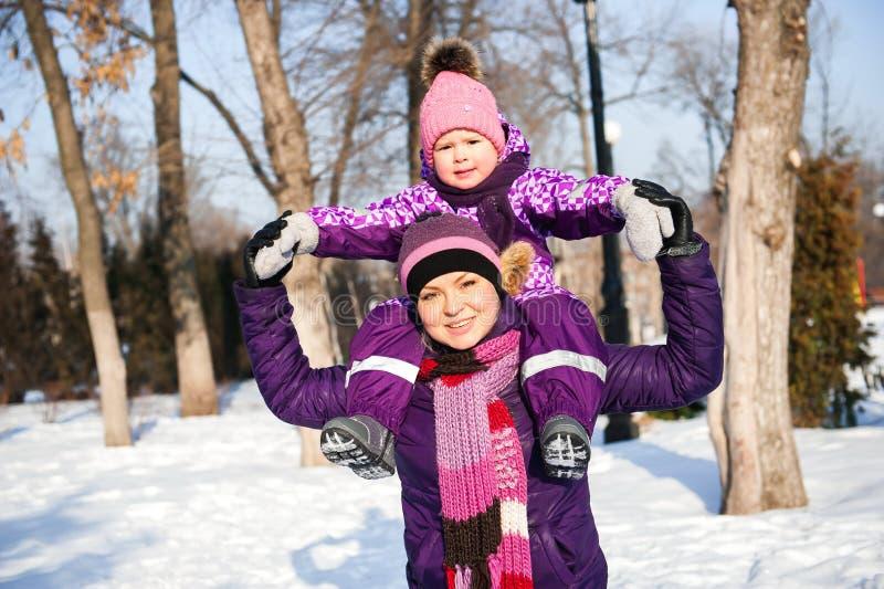 Mère et sa petite fille appréciant le beau jour d'hiver dehors photographie stock