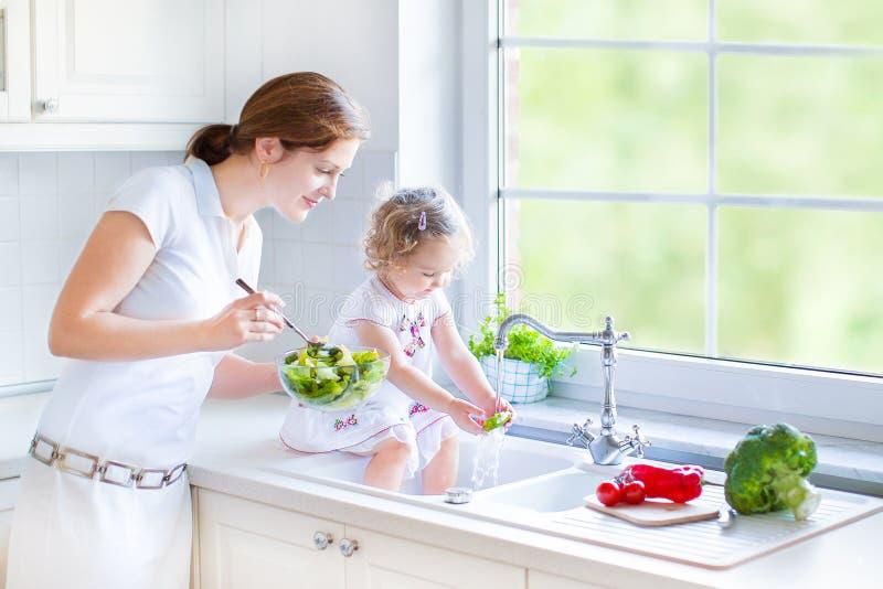 Mère et ses légumes de lavage de fille d'enfant en bas âge photographie stock libre de droits