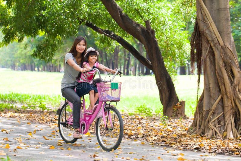 Mère et une bicyclette de recyclage de descendant photographie stock