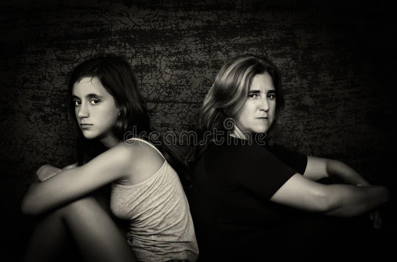 Mère fâchée et sa fille adolescente s'asseyant de nouveau au dos photos libres de droits