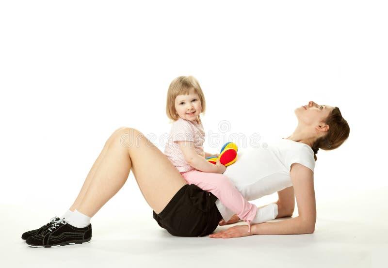 Mère faisant des exercices de sport avec son descendant image libre de droits