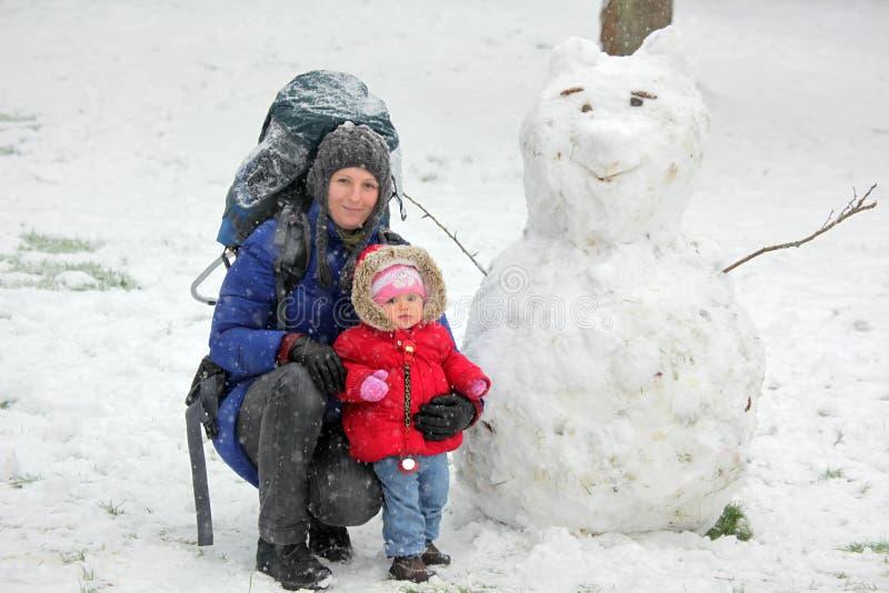 Mère, fille et bonhomme de neige image stock