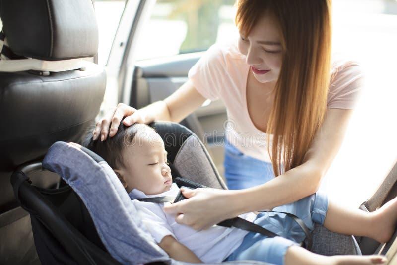 Mère fixant le bébé dans le siège de voiture photographie stock
